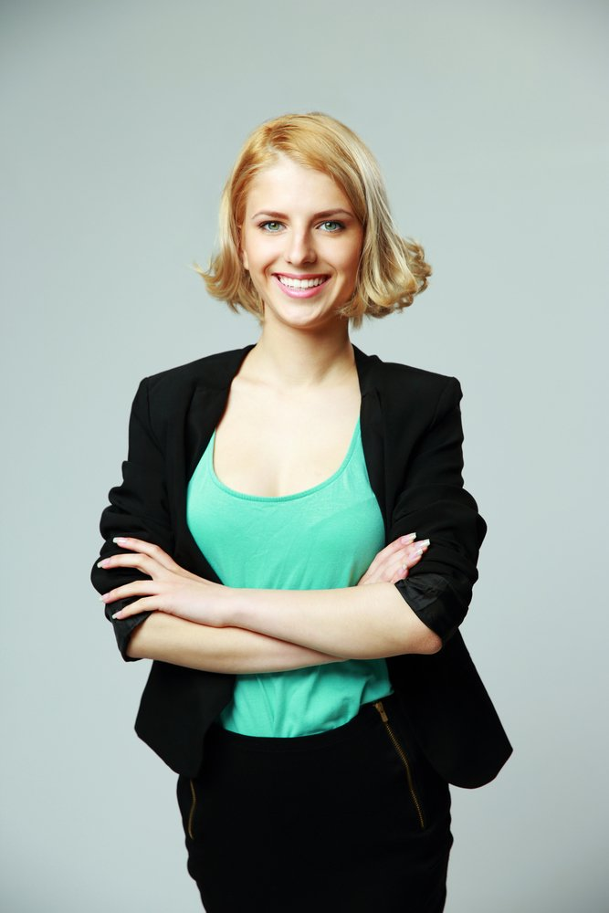 Portrait of a young happy woman with arms folded on gray background