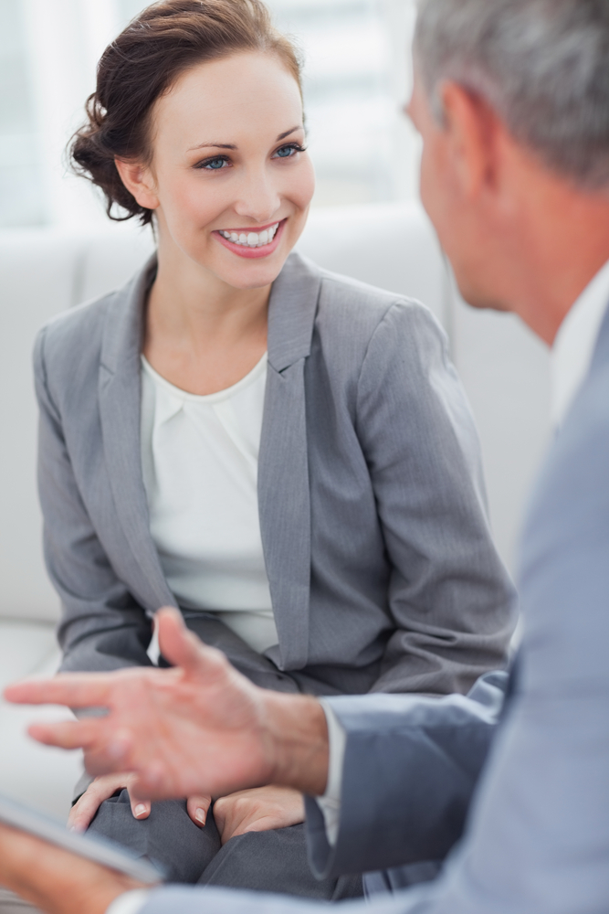 Smiling businesswoman listening to her workmate talking in bright office